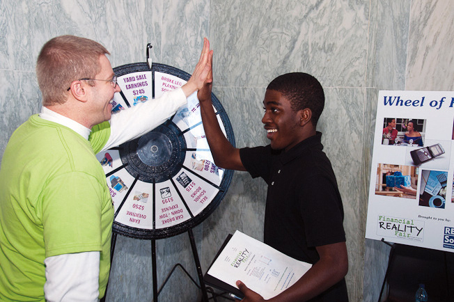 Volunteer Gerry Singleton congratulates a teen after spinning the